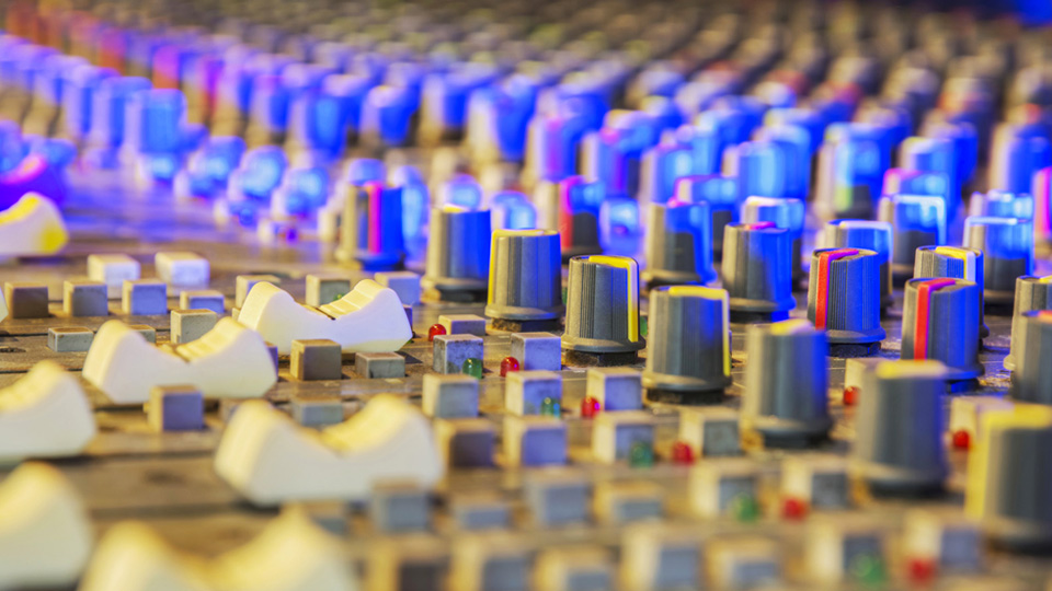 Image: close up of recording studio mixing desk.