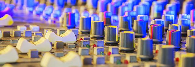 Image: close up of recording studio mixing desk.